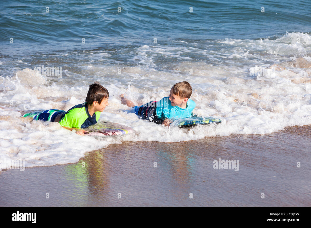 Avon, Outer Banks, North Carolina, USA.  Pre-teenage Boys in the Atlantic Surf with Boogie Boards. - Stock Image