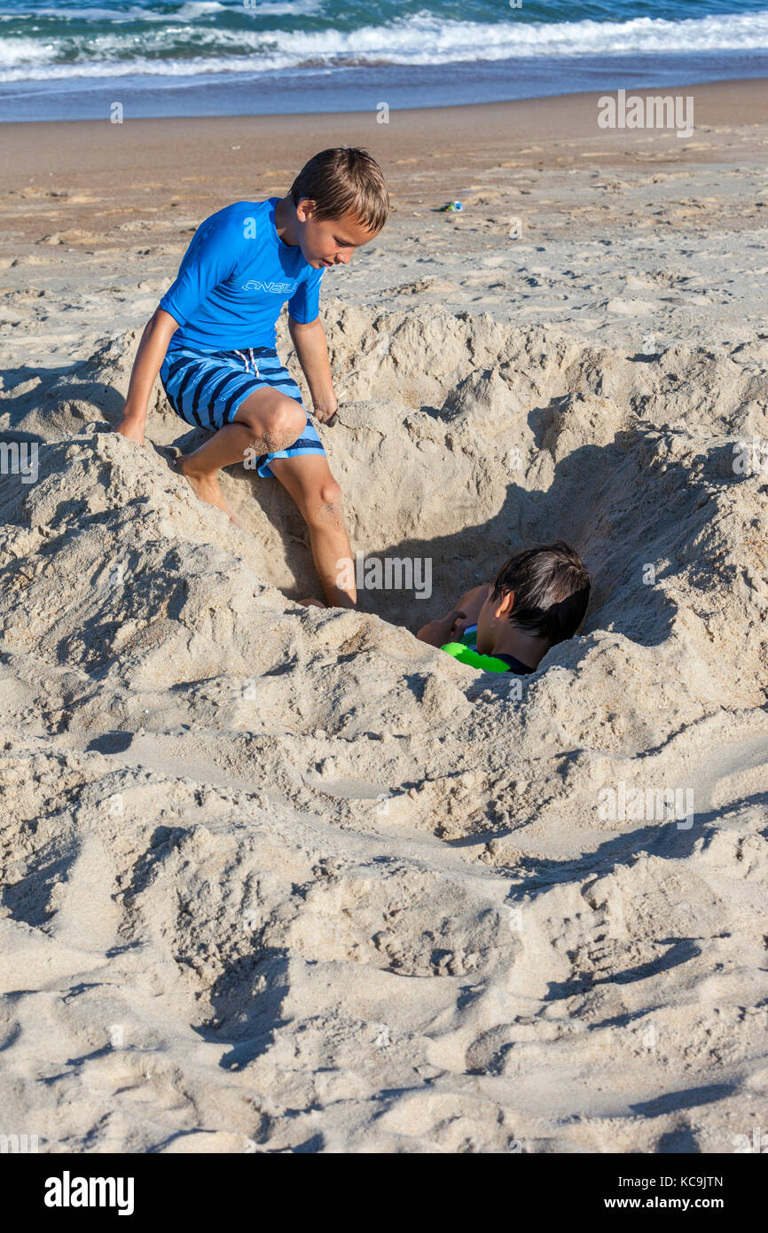 Avon, Outer Banks, North Carolina, USA.  Young Boy Checking on His Brother, Buried in the Sand. - Stock Image