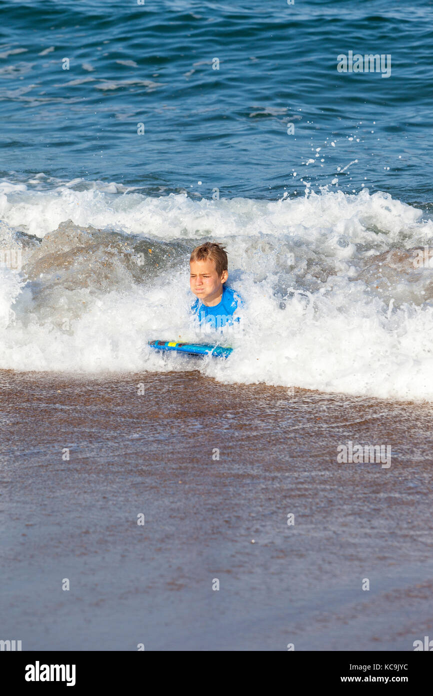 Avon, Outer Banks, North Carolina, USA.  Pre-teenage Boys in the Atlantic Surf on Their Boogie Boards. - Stock Image