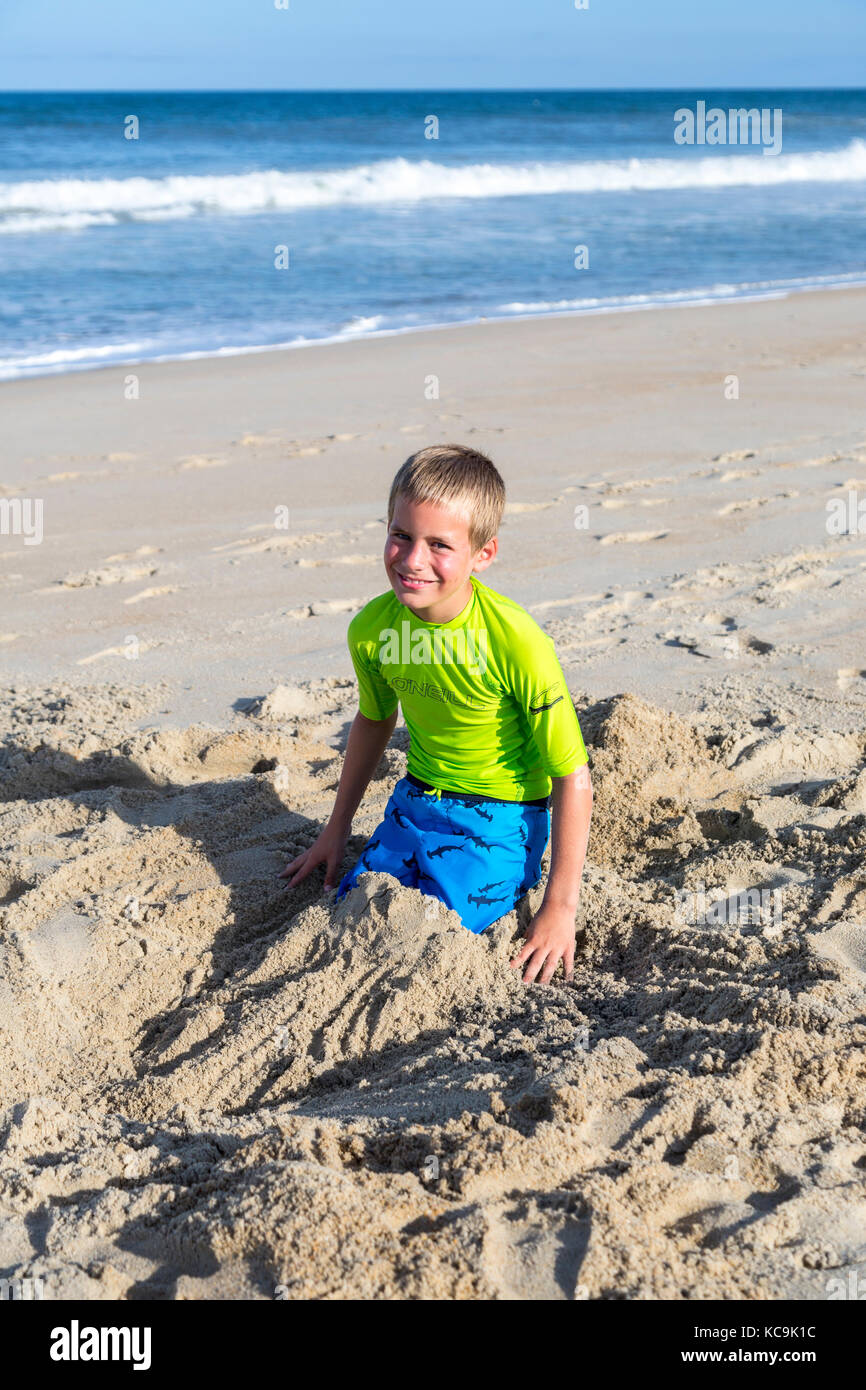 Avon, Outer Banks, North Carolina, USA.  Pre-teenage Boy Playing in the Sand on an Atlantic Beach. - Stock Image