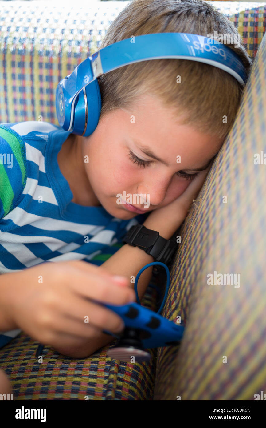 Avon, Outer Banks, North Carolina, USA.  Young American Boy Playing with his Mobile Game Device. - Stock Image