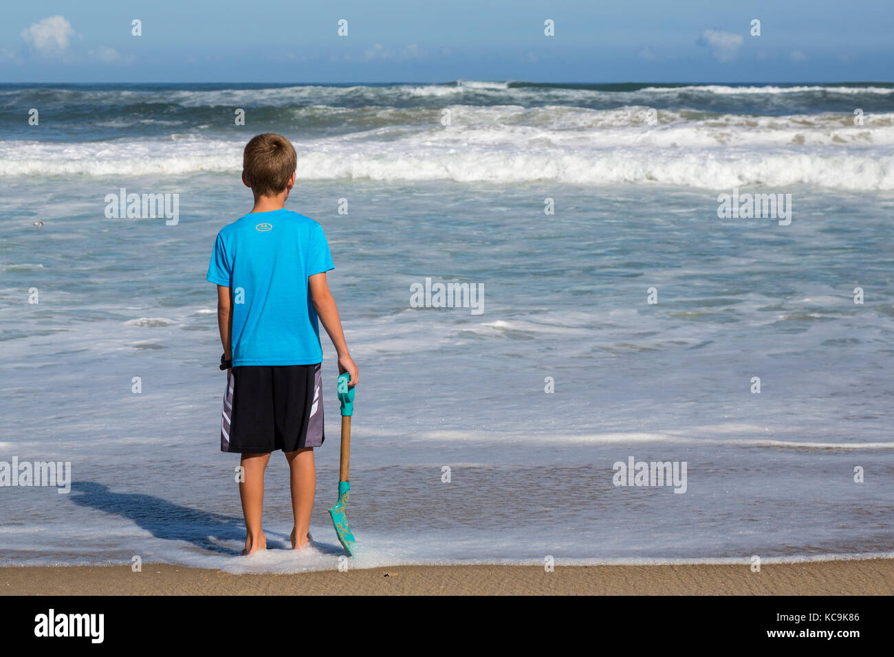 Avon, Outer Banks, North Carolina, USA.  Young Boy Contemplating the Atlantic Waves. - Stock Image