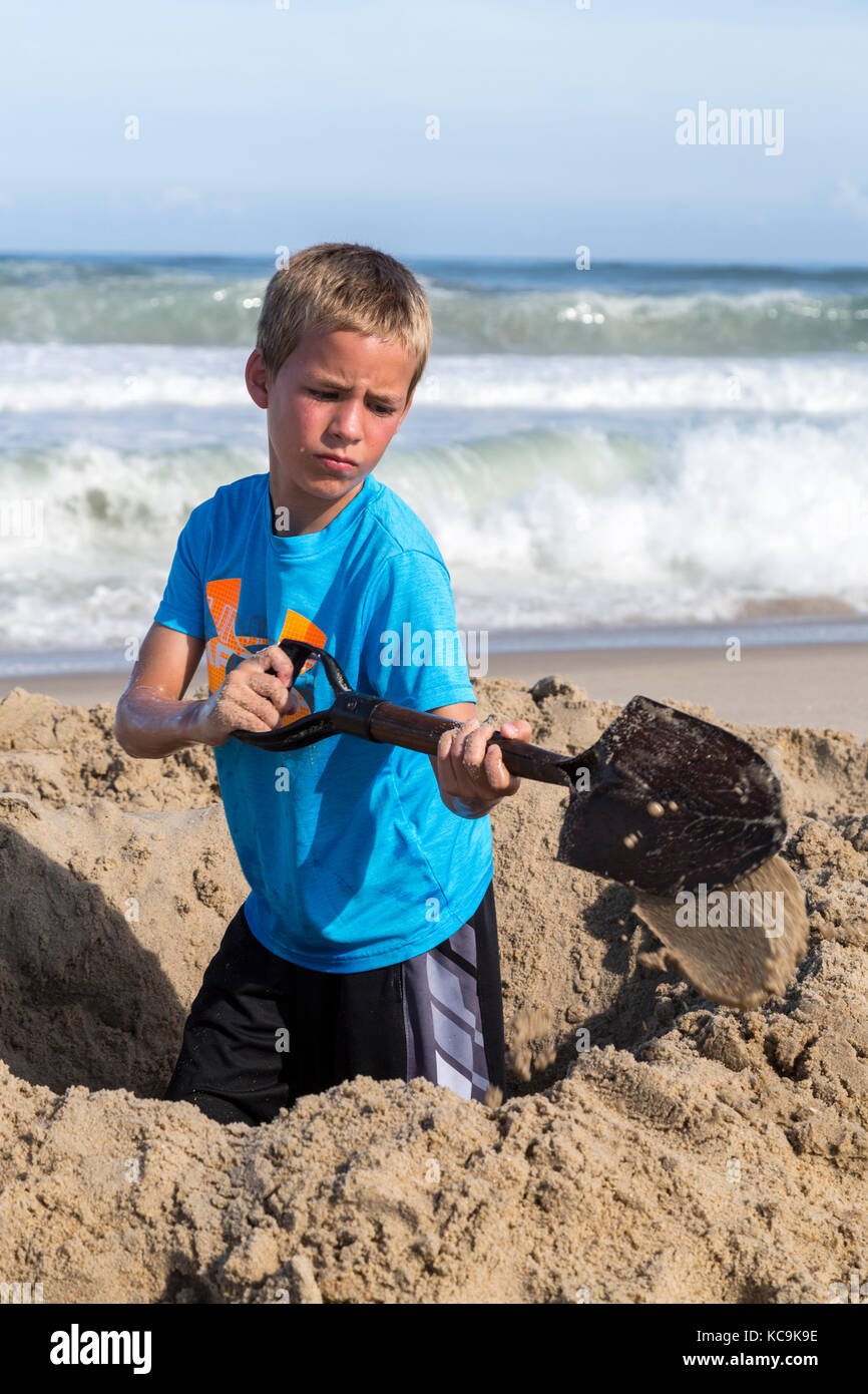 Avon, Outer Banks, North Carolina, USA.  Young Boy Digging a Hole in the Sand. - Stock Image