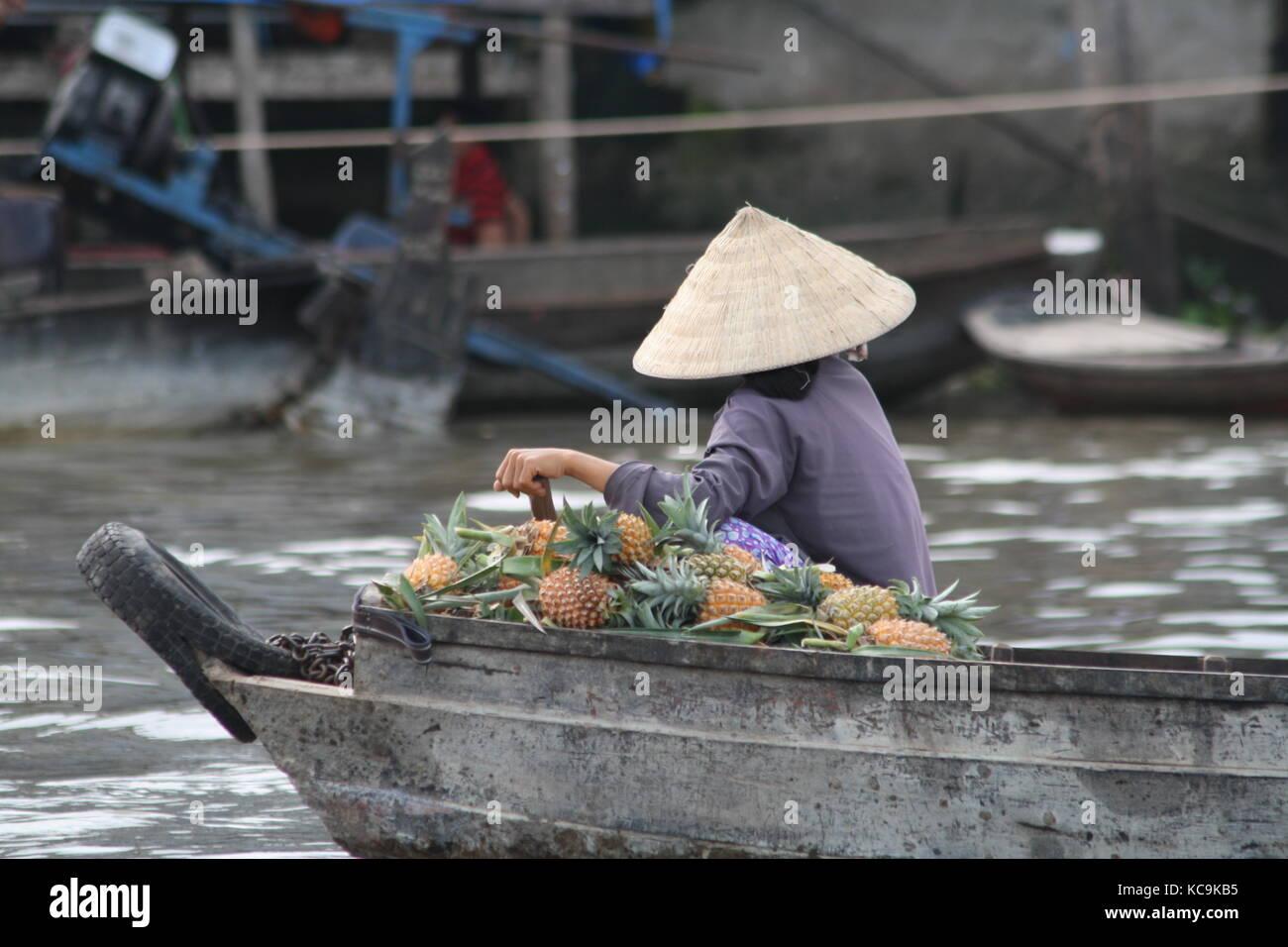 Frau mit  einem vollen Boot ananas Frau mit  einem vollen Boot ananas - Woman with a full boat of pineapple - Stock Image