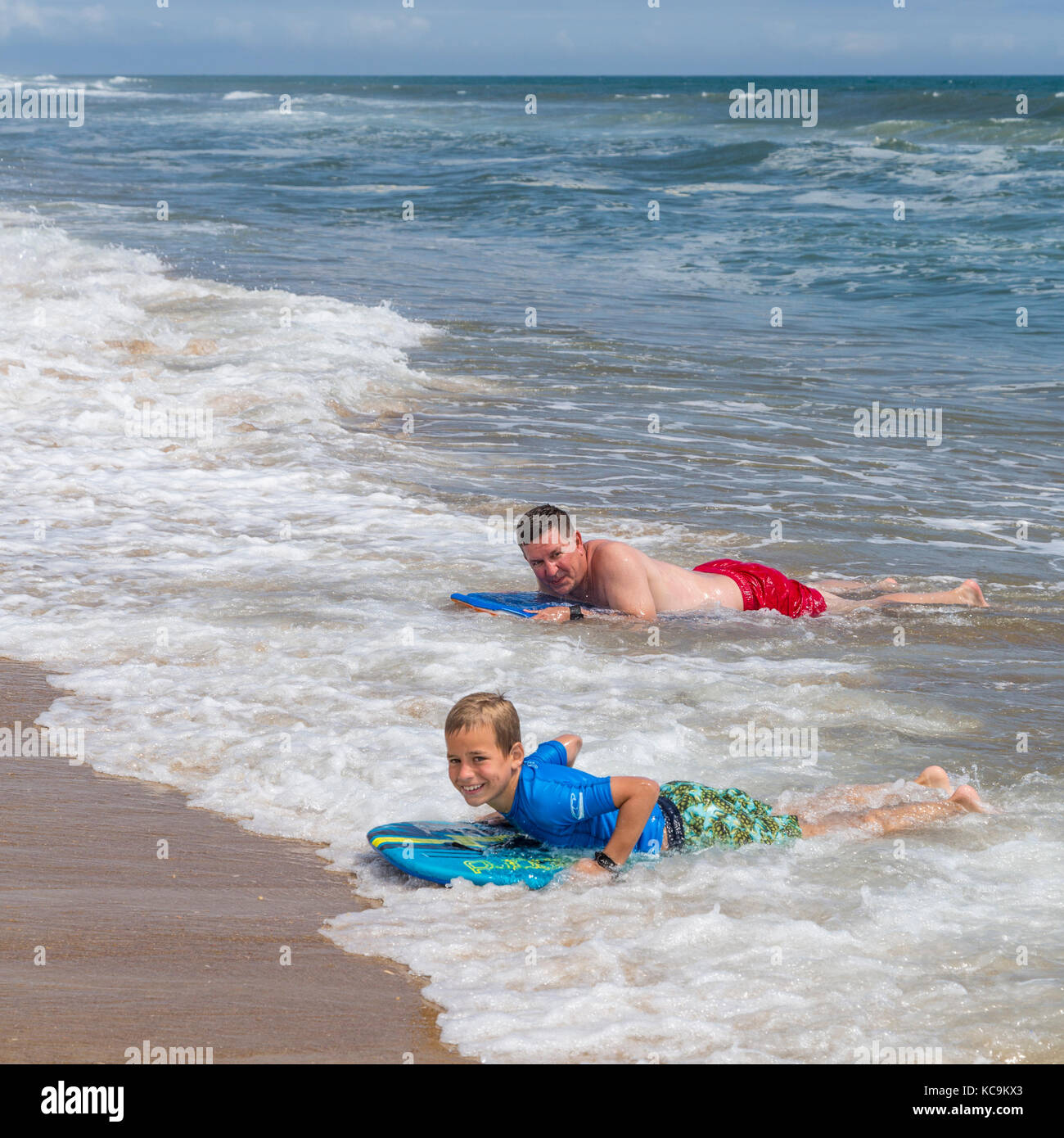 Avon, Outer Banks, North Carolina, USA.  Father and Son Landing on the Beach with their Boogie Boards. - Stock Image