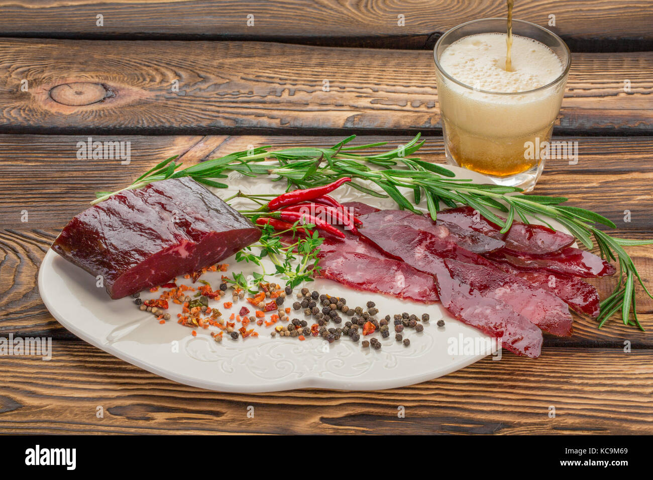 Dry meat with fresh herbs, chilli, condiments on a plate. beer is poured into a glass over wooden background. Beer Stock Photo