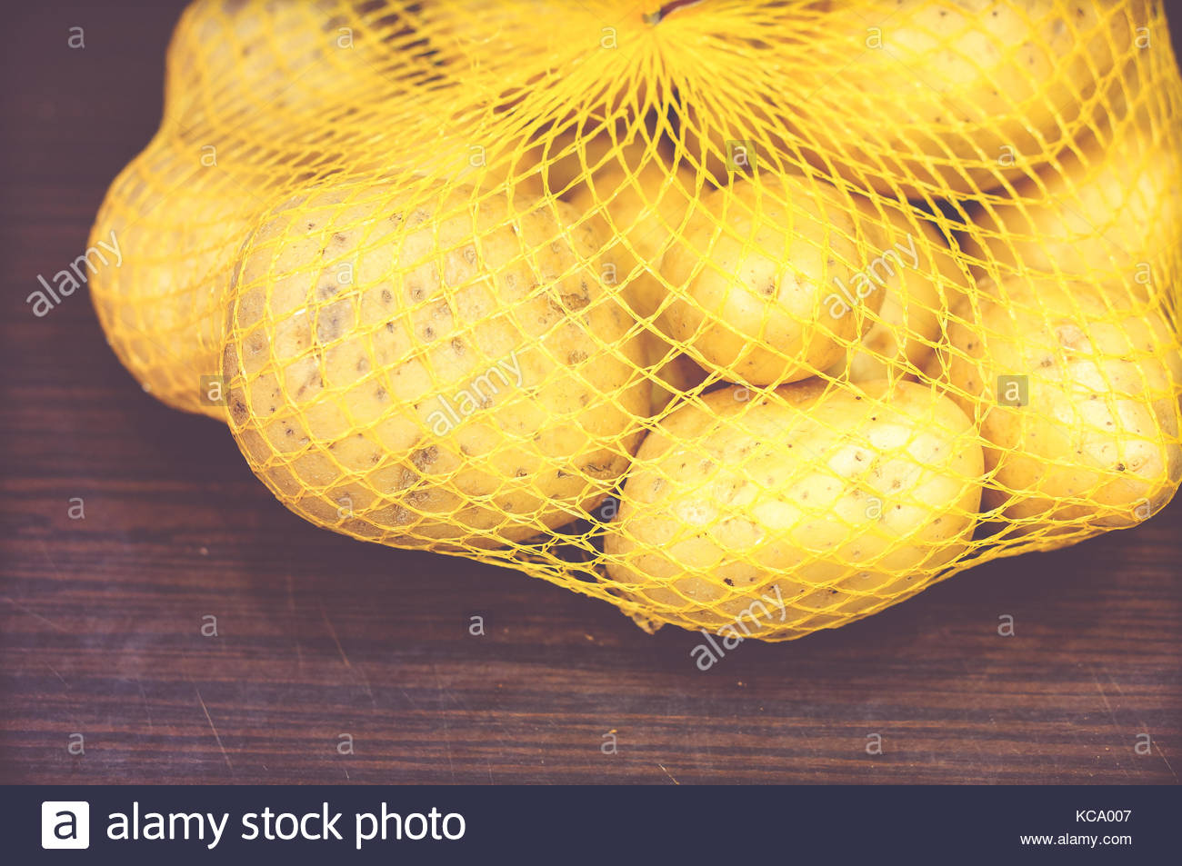 Fresh potatoes in a net on wooden table in soft focus - Stock Image