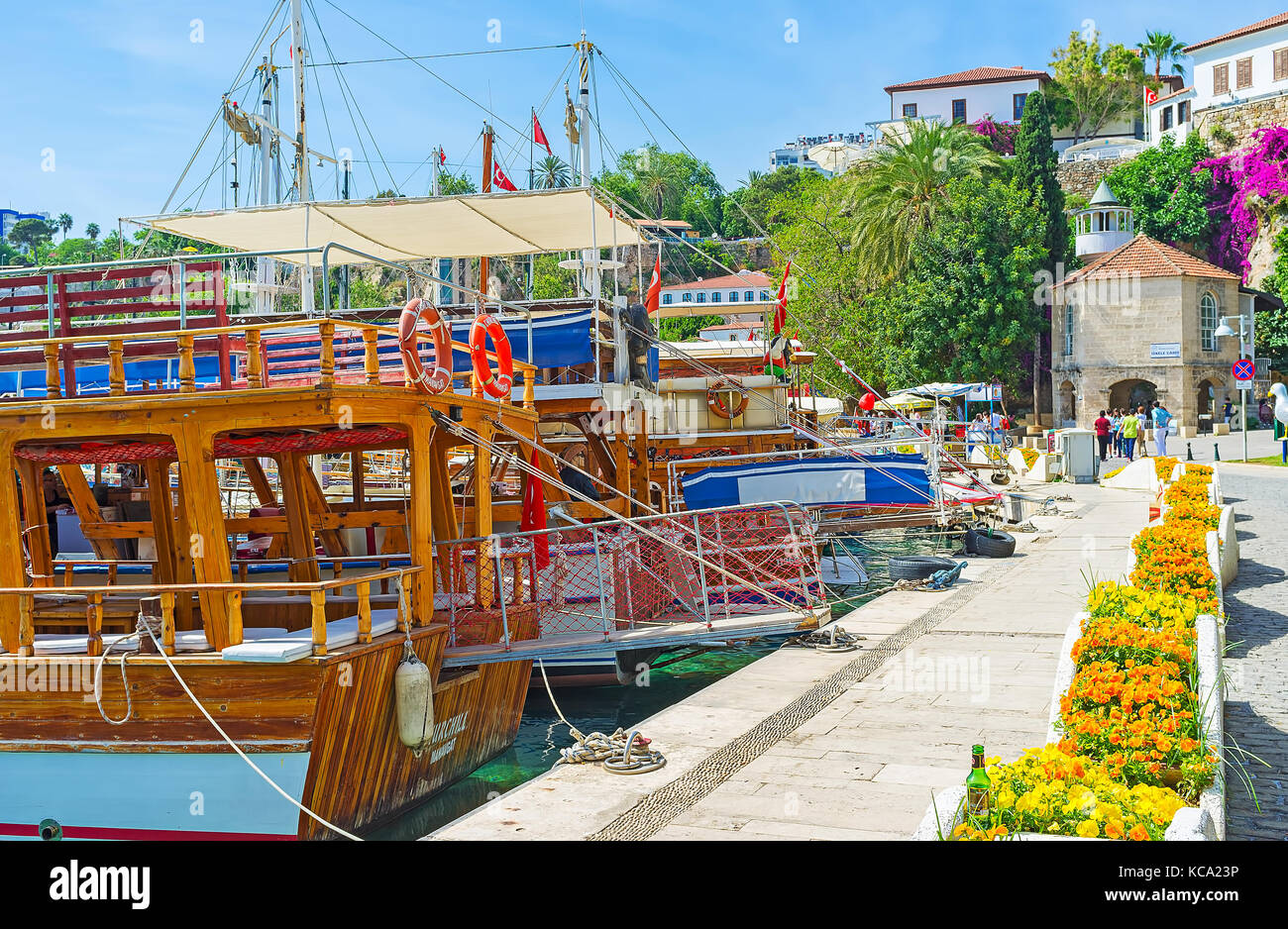 ANTALYA, TURKEY - MAY 12, 2017: The walk along the tourist boats in old marina with a view on historic Iskele Mosque, - Stock Image