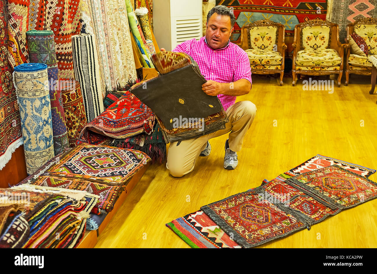 ANTALYA, TURKEY - MAY 12, 2017: The vendor of carpet store demonstrates the antique hand knotted camel saddle bags, - Stock Image