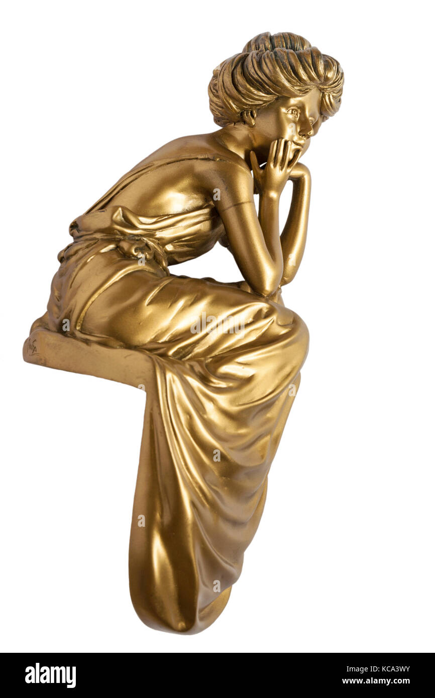 gold coloured ornament of woman with chin in hands sitting wearing long dress isolated on white background - Stock Image