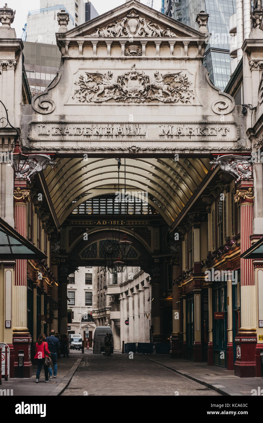 Couple walking into Leadenhall Market, popular market in London that was built in the 19th century. - Stock Image