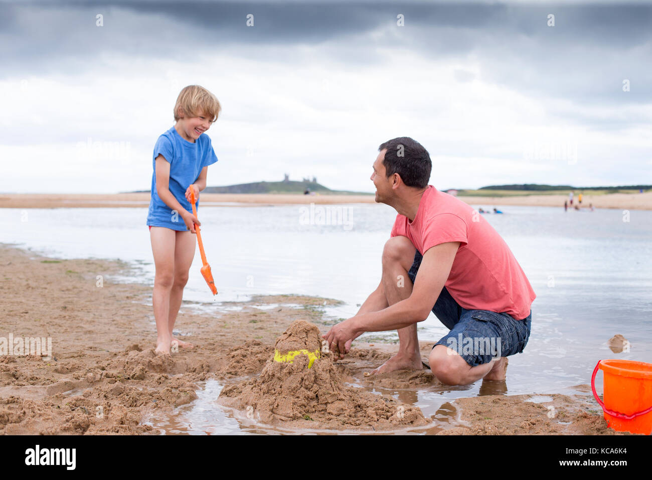 A father and son are building sand castles on the beach - Stock Image