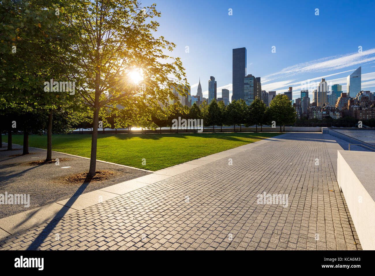 Sunset with  Manhattan Midtown East from paved walkway of Franklin D. Rosevelt Four Freedoms Park. Roosevelt Island, - Stock Image