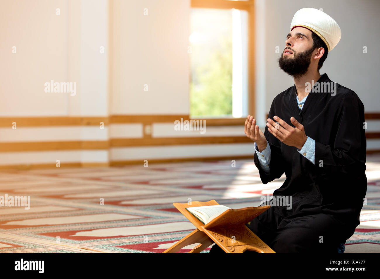 Religious muslim man praying inside the mosque - Stock Image