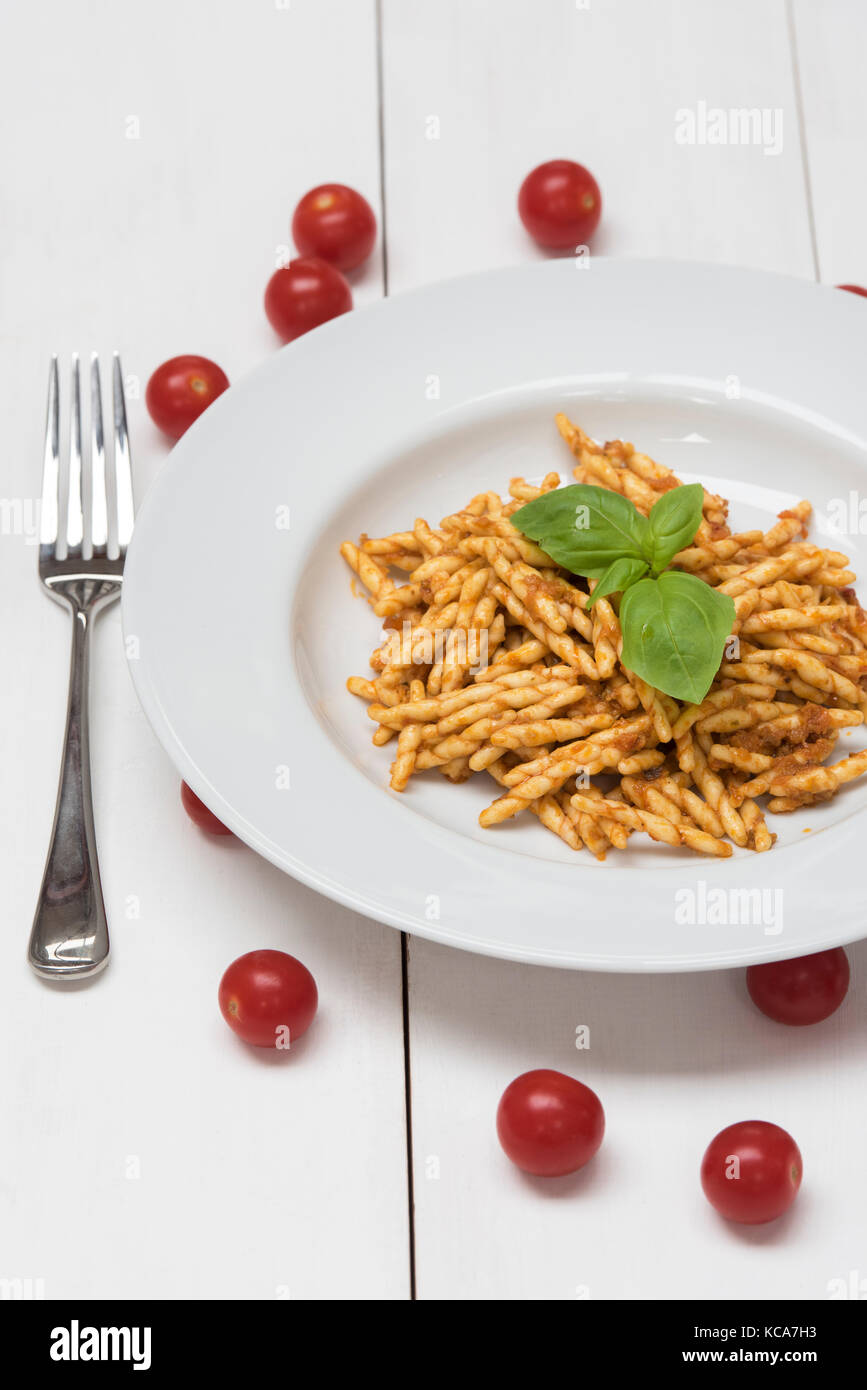 Trofie, pasta with tomato paste, basil and tomatoes on a white background - Stock Image