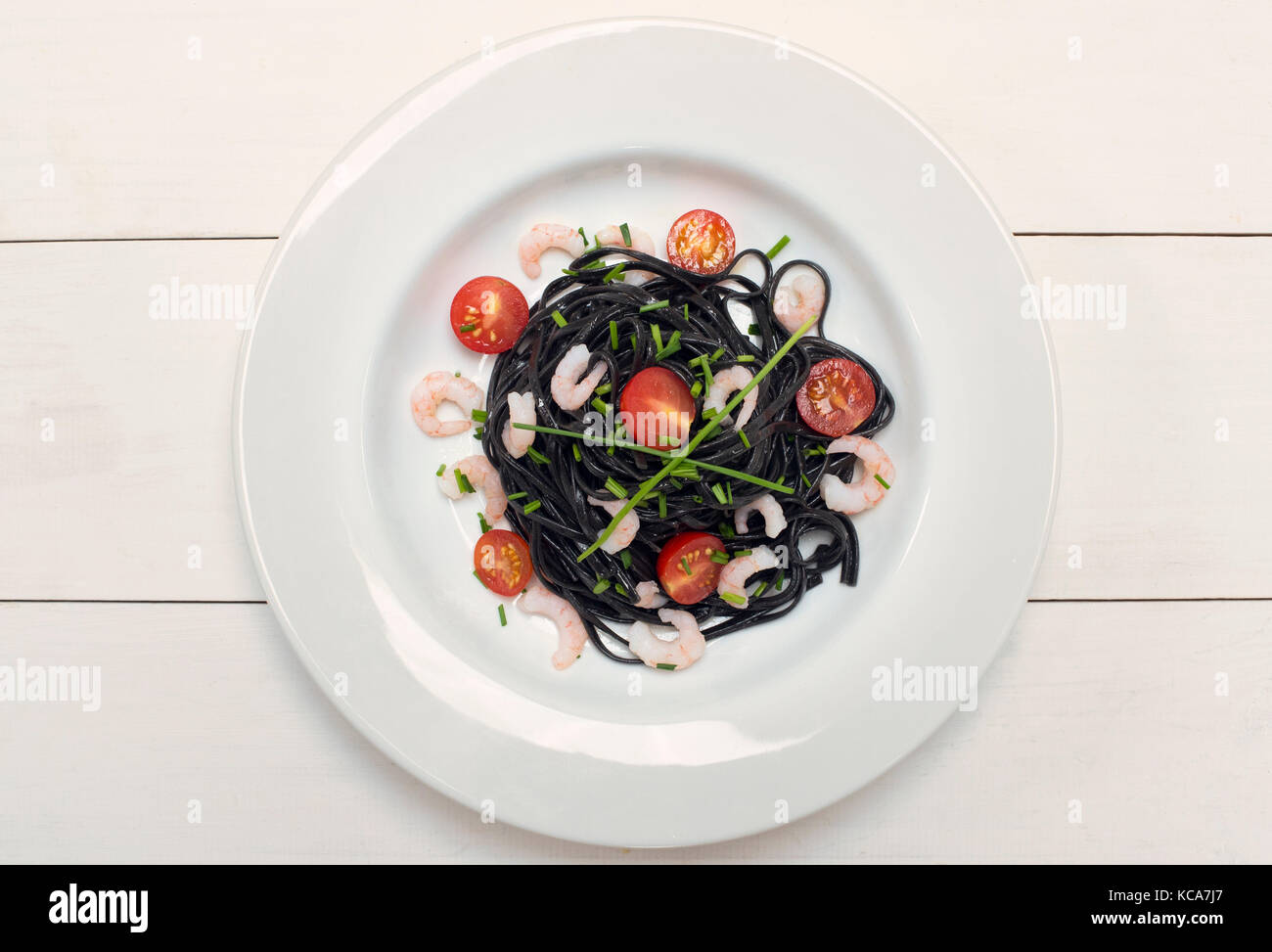 Squid ink black pasta with prawns, chives and tomatoes on a white background Stock Photo