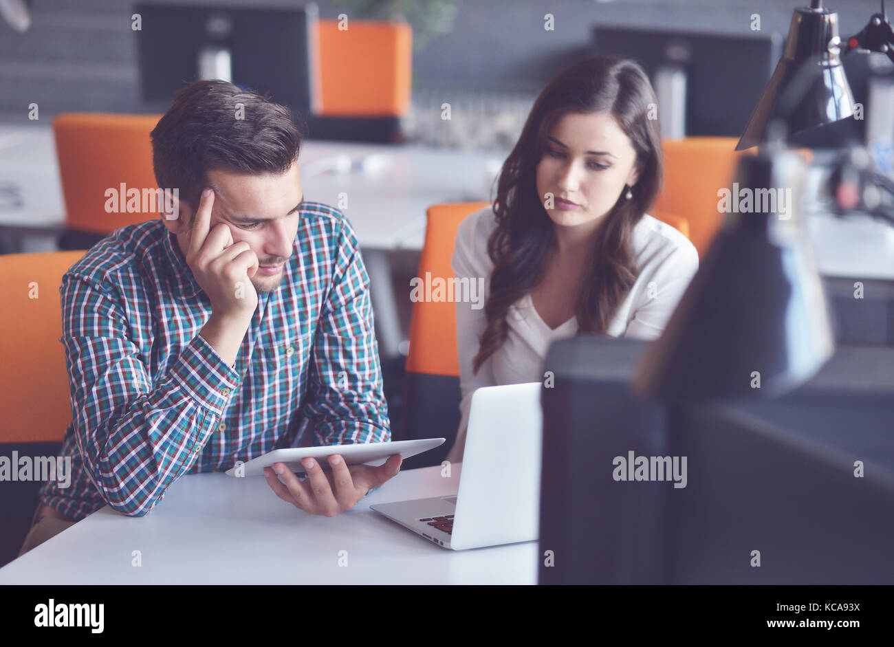 Young Casual business couple using computer in the office. Coworking, Creative manager showing new startup idea - Stock Image