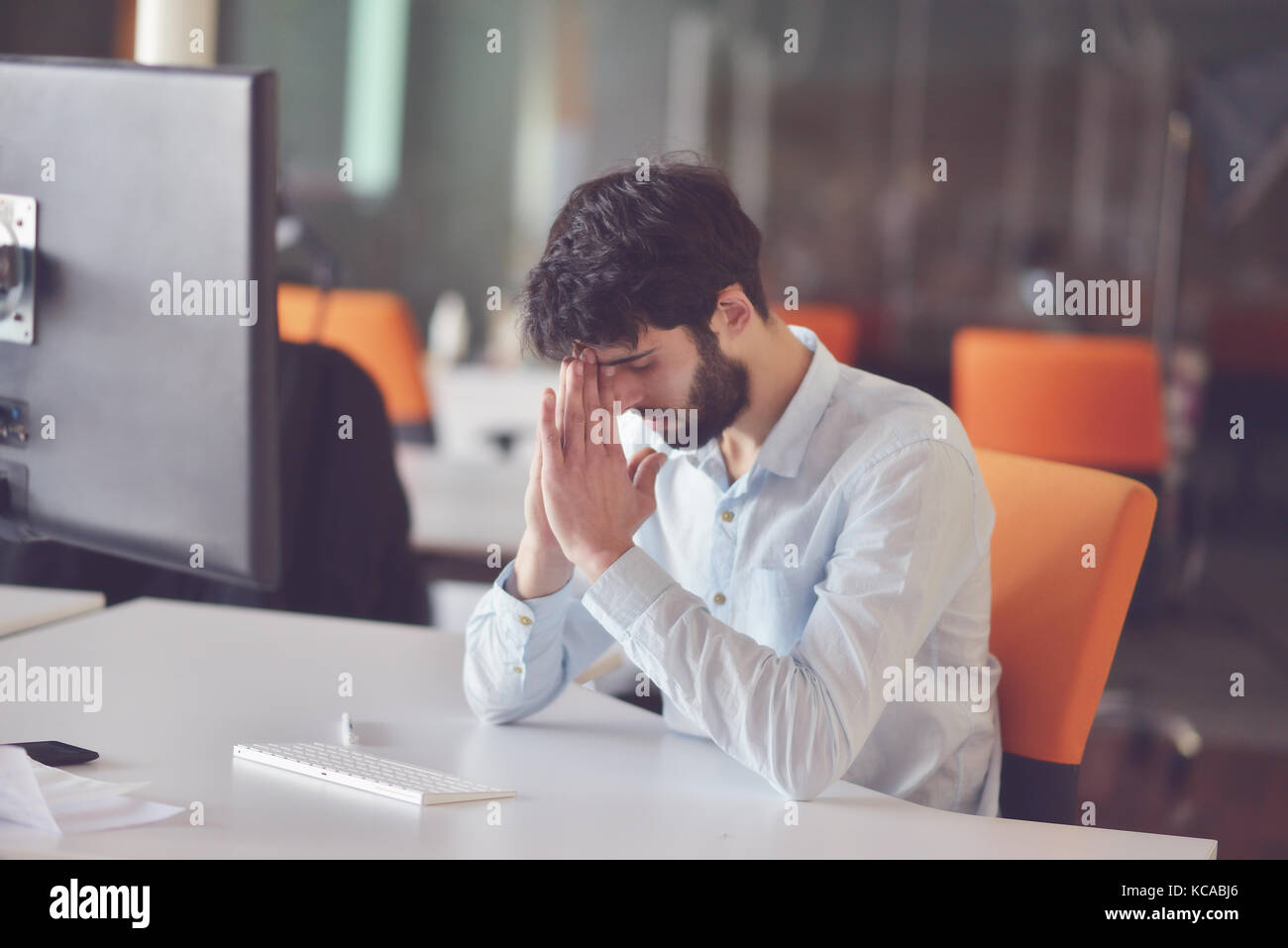 young business man working on desktop computer at his desk in modern bright startup office interior - Stock Image