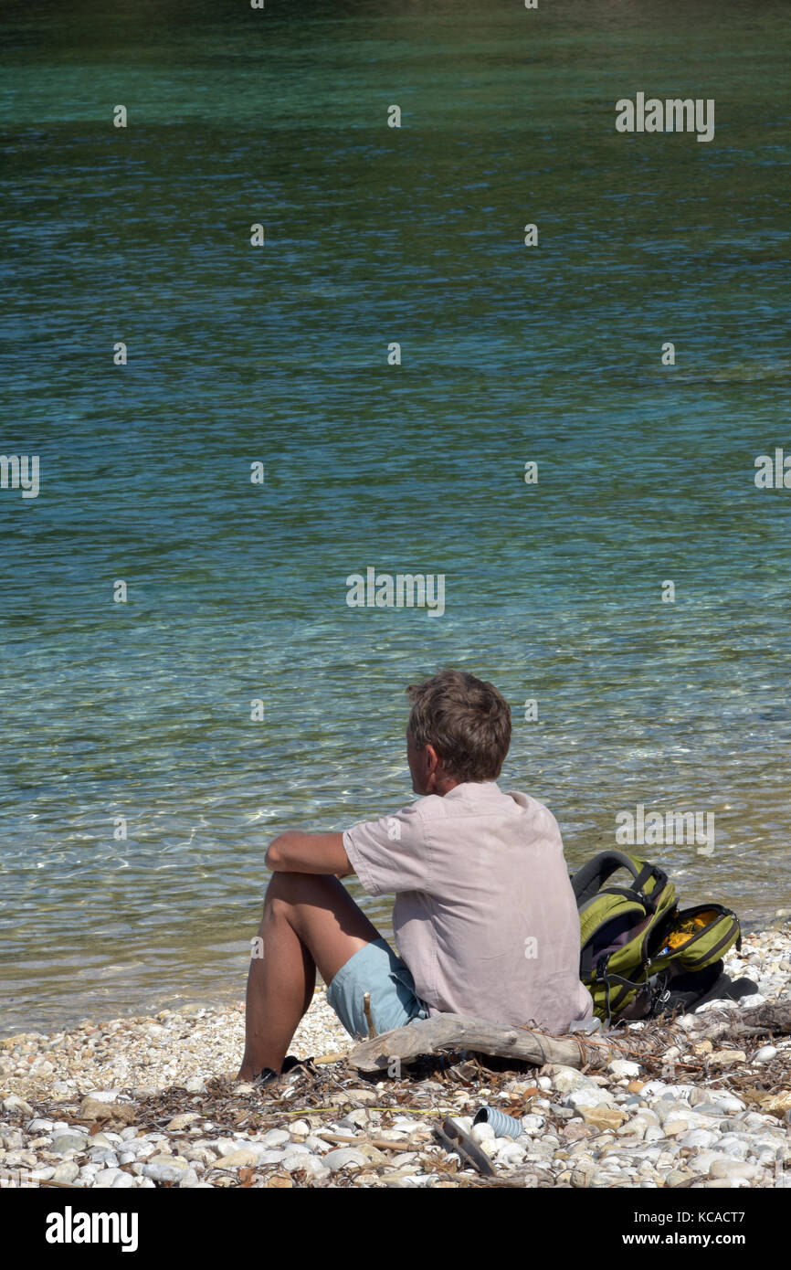 a man sitting on the beach on his own. Thinking time alone. - Stock Image