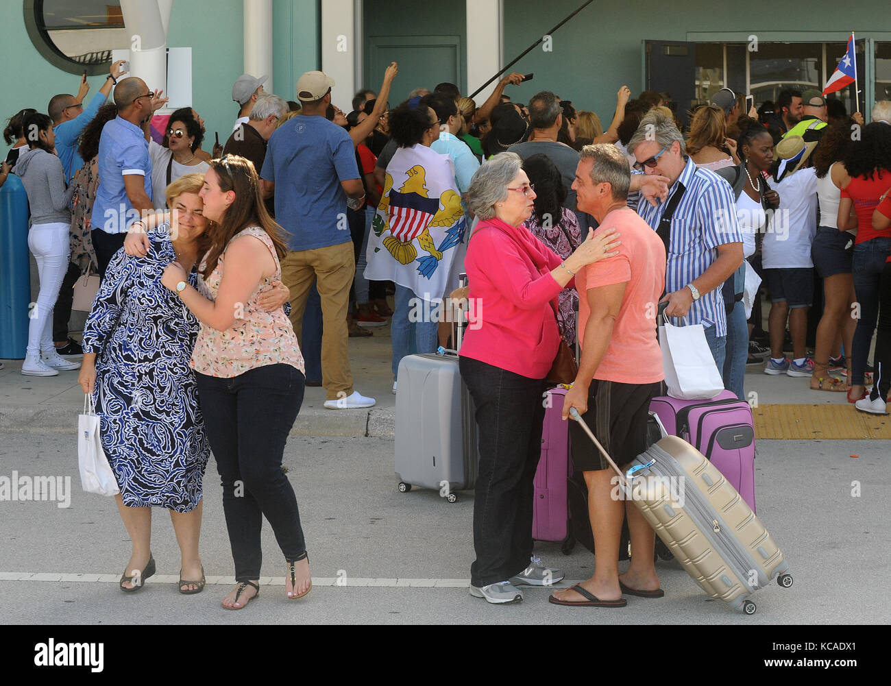 Fort Lauderdale, Florida, USA. 03rd Oct, 2017. Victims of Hurricane Maria embrace with waiting family members at - Stock Image