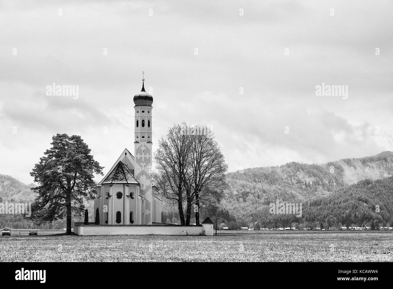 Old church with high bell tower and graveyard bellow mountains.  April weather. Wet spring snow in already fresh - Stock Image