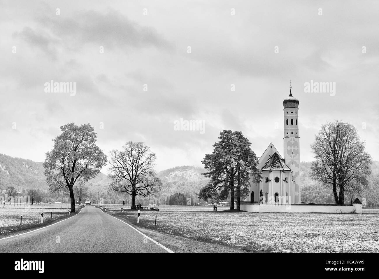 Old church and graveyard.  Straight  asphalt way at meadows. April weather. Wet spring snow in already fresh green - Stock Image