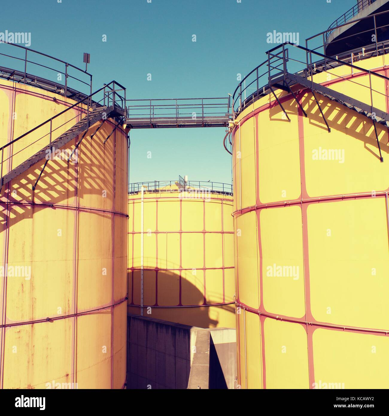Old metal sheets l tanks in powerplant, old kind of factory plant. Metal construction with old yellow paint and - Stock Image