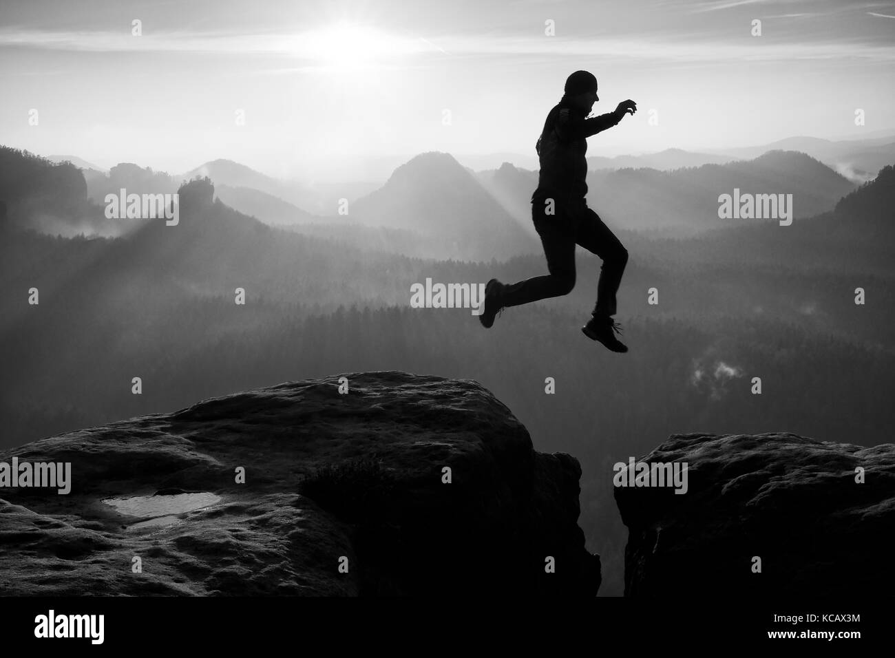 Hiker in black is jumping between rocky peaks. Amazing activities in rocky mountains, heavy mist in deep valley. - Stock Image