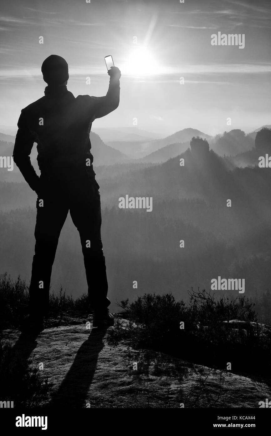 Man takes photos with phone on rock empire. Dreamy fogy mountains, spring orange pink misty sunrise in a beautiful - Stock Image
