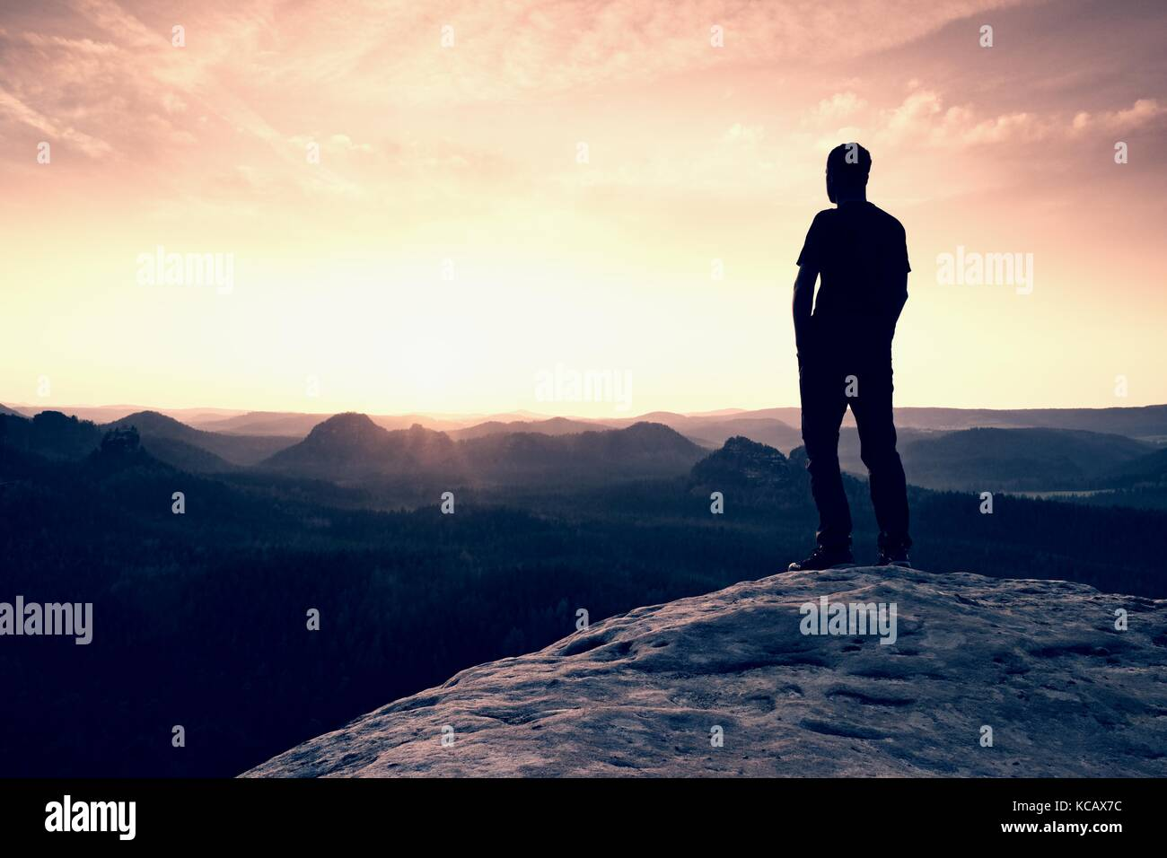 Silhouette of Confident and Powerful Man Standing with Hands on Hips, Late Day Sun with Copy Space - Stock Image