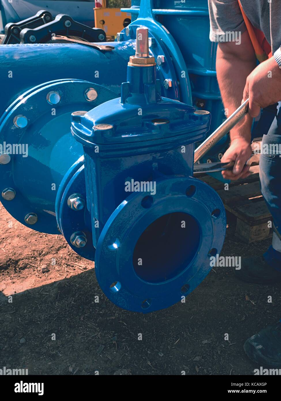 Worker hands screwing Gate valve with nuts on new dring water piping.  Water suply construction with new Gate valves - Stock Image