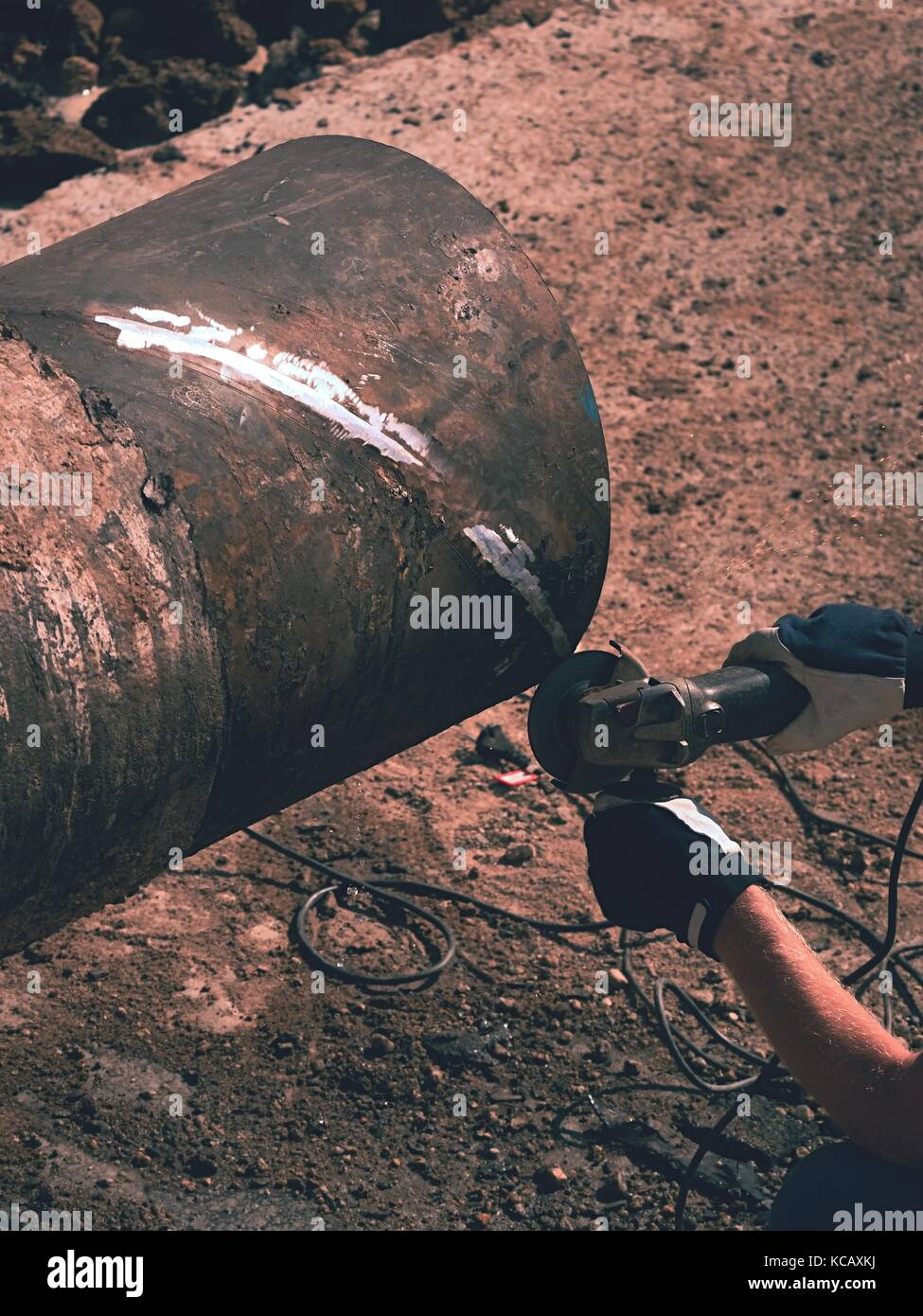 Worker underground with hand grinder is cutting big metal tube. Sparks are flying down to wet clay. Working staff Stock Photo