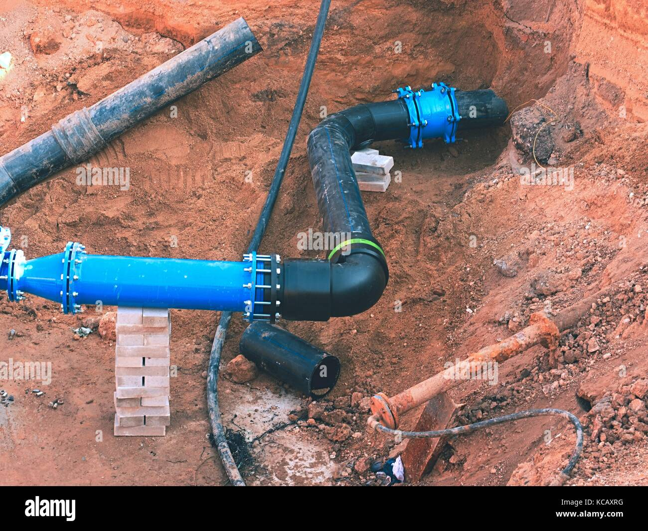 Repairing process of underground water supply pipeline.  Black plastic tubes in trench of sand joined with steel - Stock Image