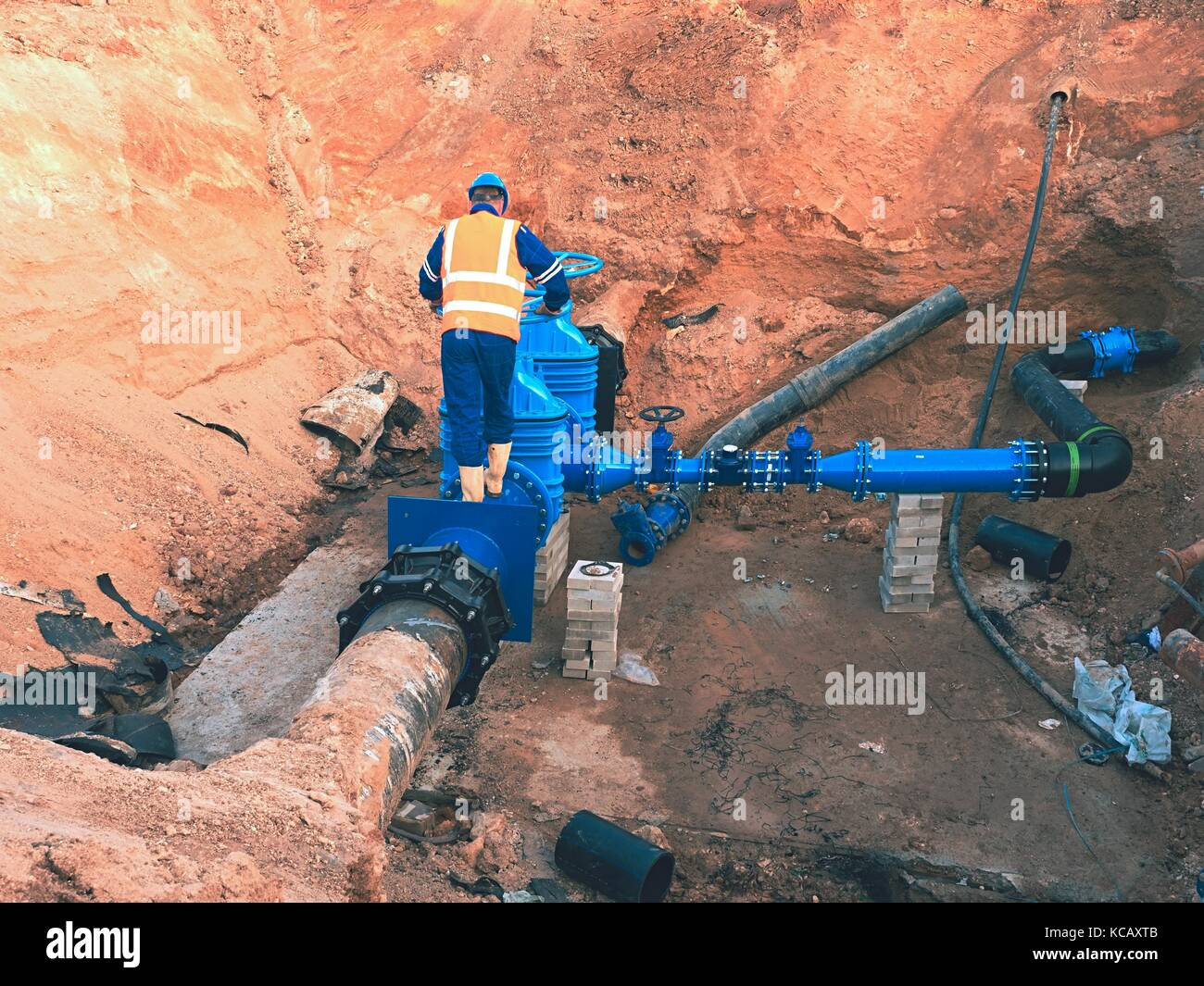 Worker in safety clothes drive valve conduit  on City potable water pipe  joined with new black waga multi joint - Stock Image