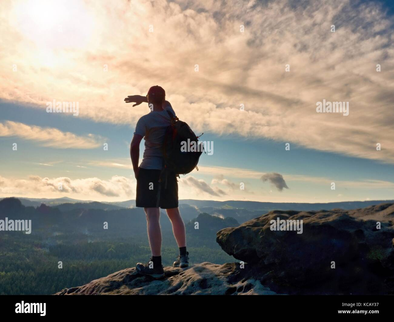 Man shadowing eyes. Alone tourist with red  baseball cap sporty backpack stand on cliff edge and watching into deep - Stock Image