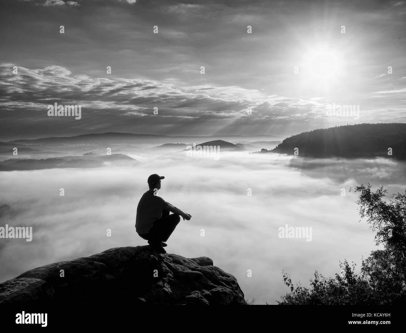 Moment of loneliness. Man sit on rock and watching into colorful mist and fog in valley. Man hiking. Sad person - Stock Image