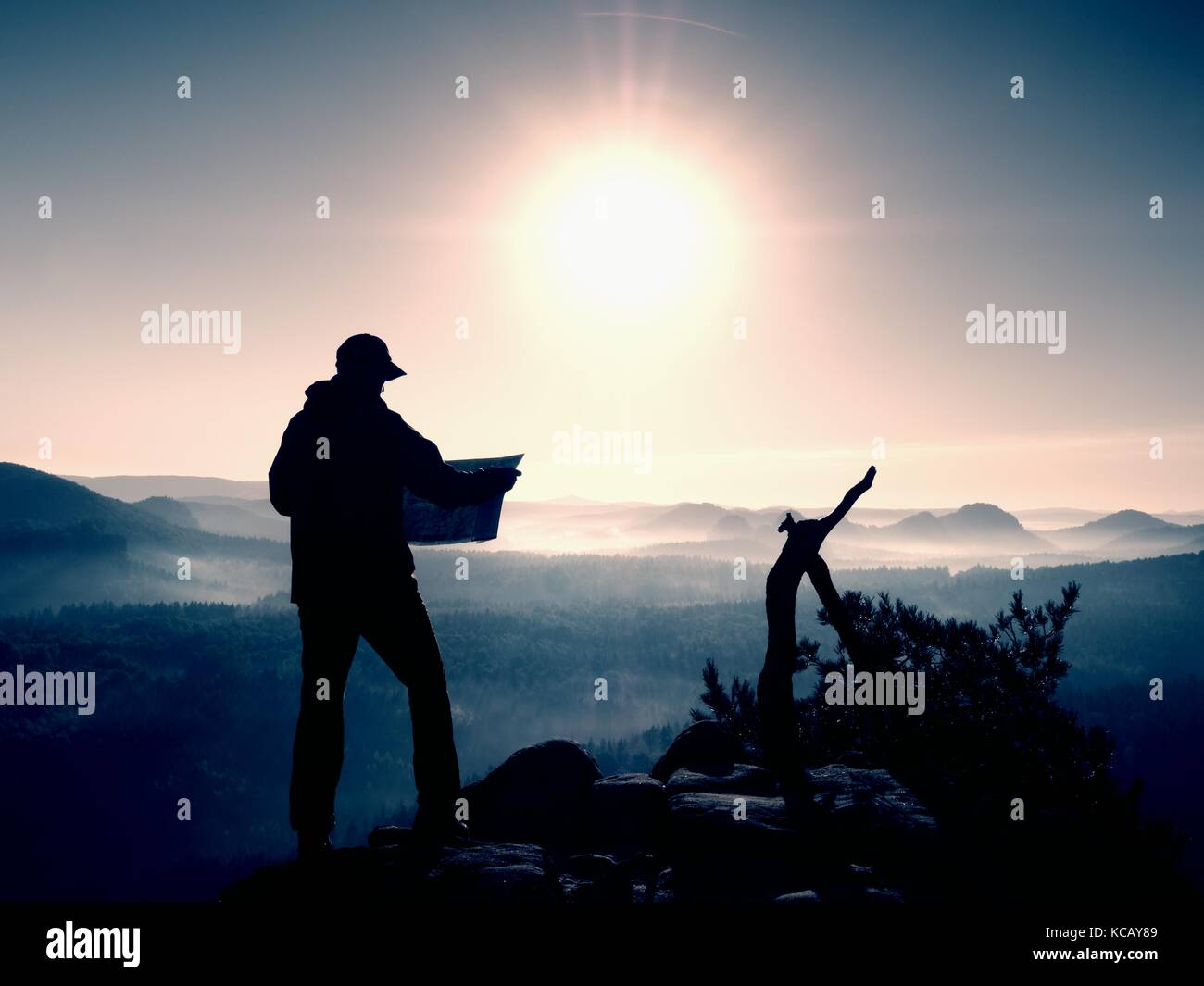 Tall tourist guide looking in paper  map. Wild hilly nature park. Hiker is  hiking.  Man hiker with heavy backpack. - Stock Image