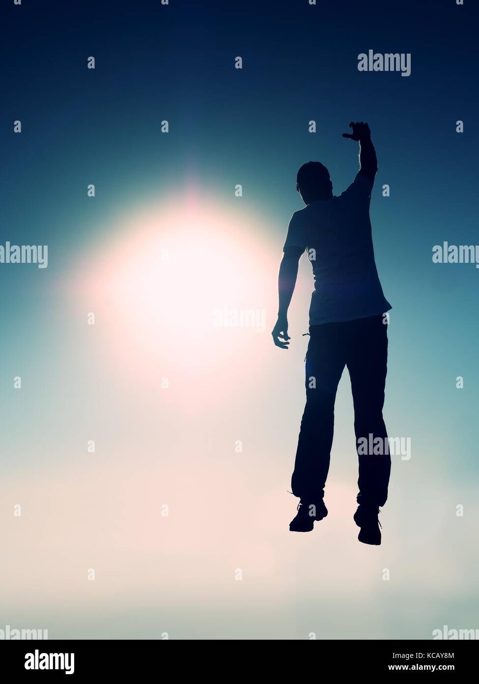 Crazy man is flying over Sun on blue sky background. Silhouette of jumping man and beautiful sunset sky. Element - Stock Image