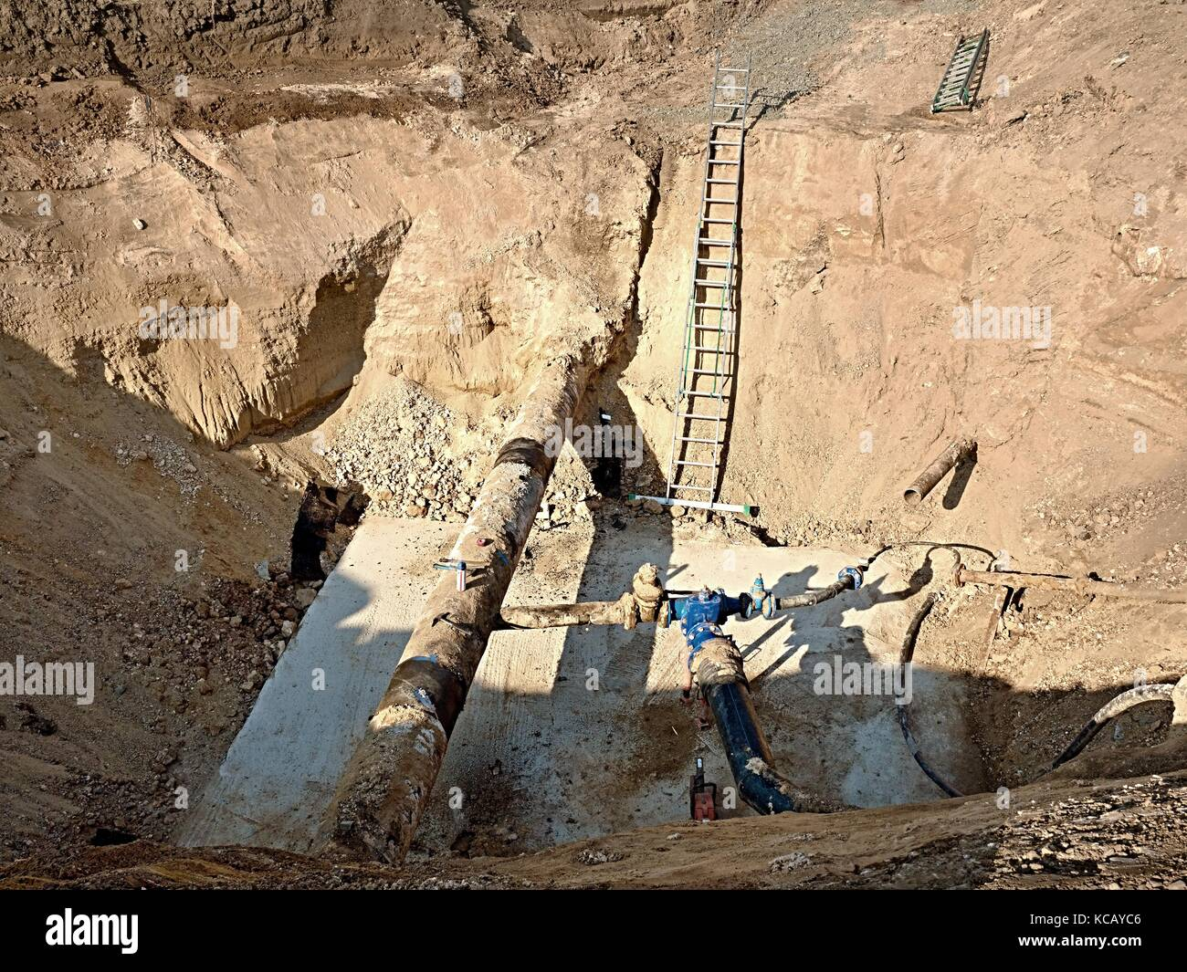 Excavation pit. Old 500mm drink water pipe with 150mm  cornering arm with gate valves, corroded  joining fittings. - Stock Image