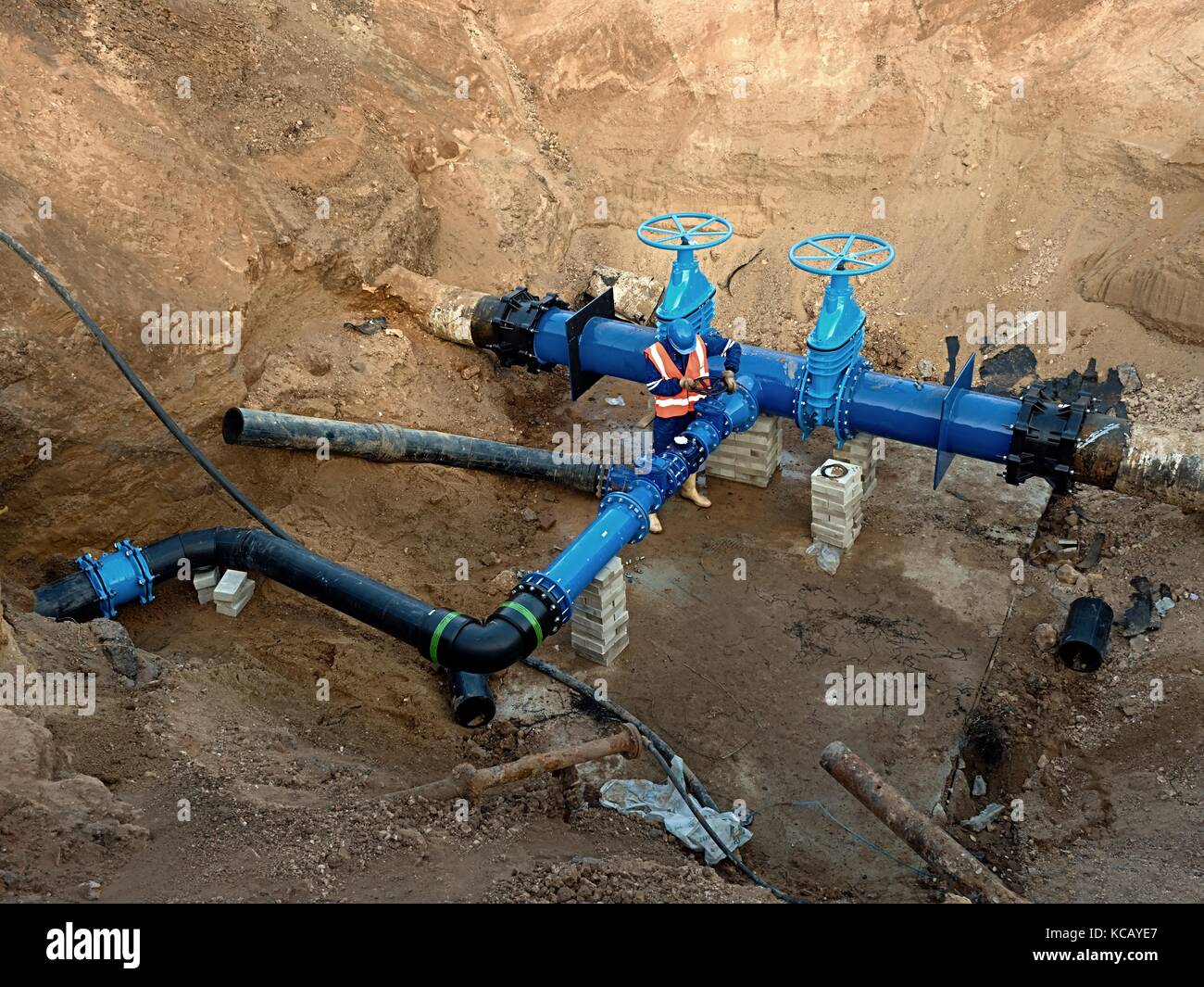 Technical expert open gate valve on 500mm drink water pipes joined with new black waga multi joint members into - Stock Image