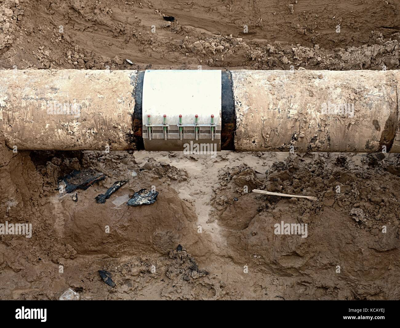 Old big drink water pipes joined with  stainless repairing sleeve members. Finished repaired piping waiting for - Stock Image
