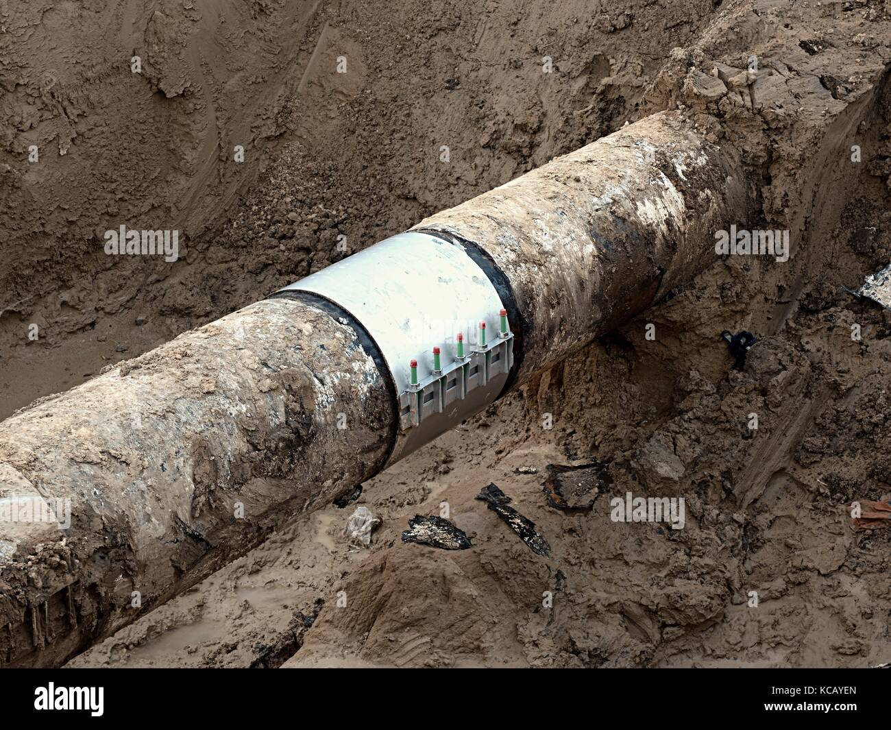 Excavation pit. Old drink water pipe with  stainless repairing sleeve members. Finished repaired piping waiting - Stock Image