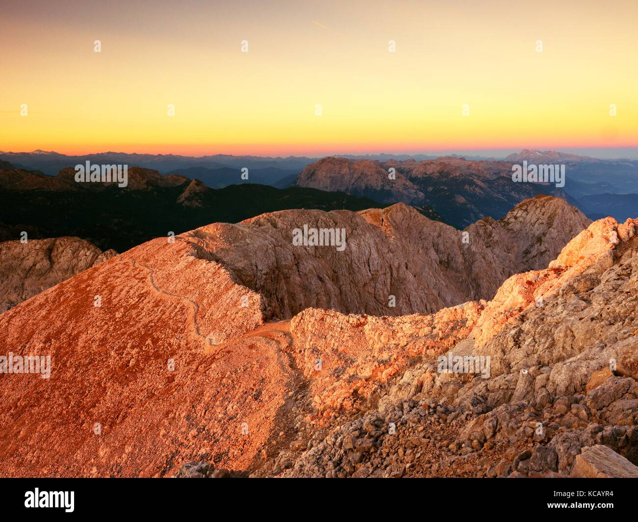 Morning view over Apine  cliff and valley.Daybreak Sun at horizon. Mountains increased from foggy background - Stock Image
