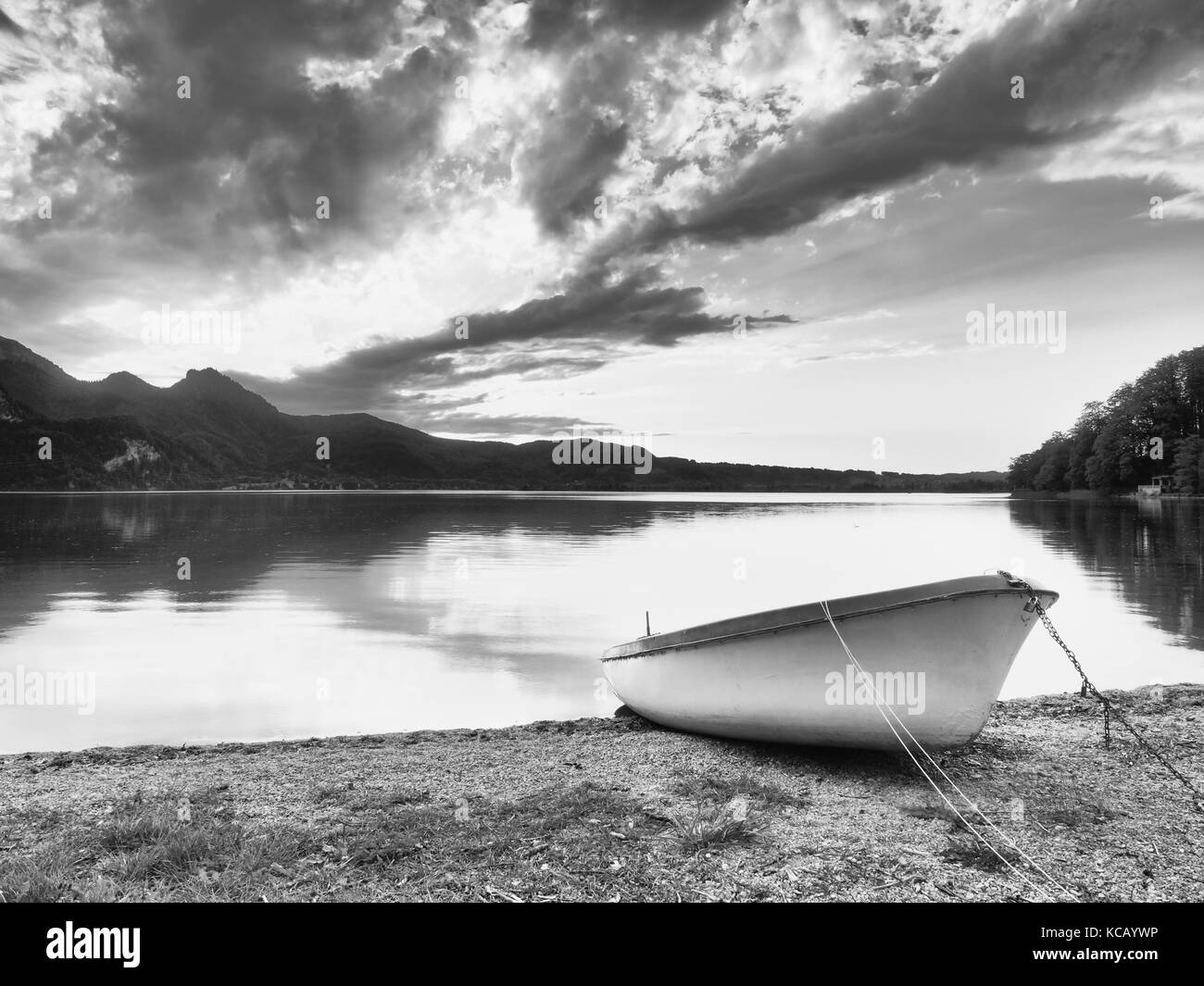 Abandoned white paddle boat on Alps lake bank. Evening lake glowing by sunlight. Dramatic and picturesque scene. - Stock Image
