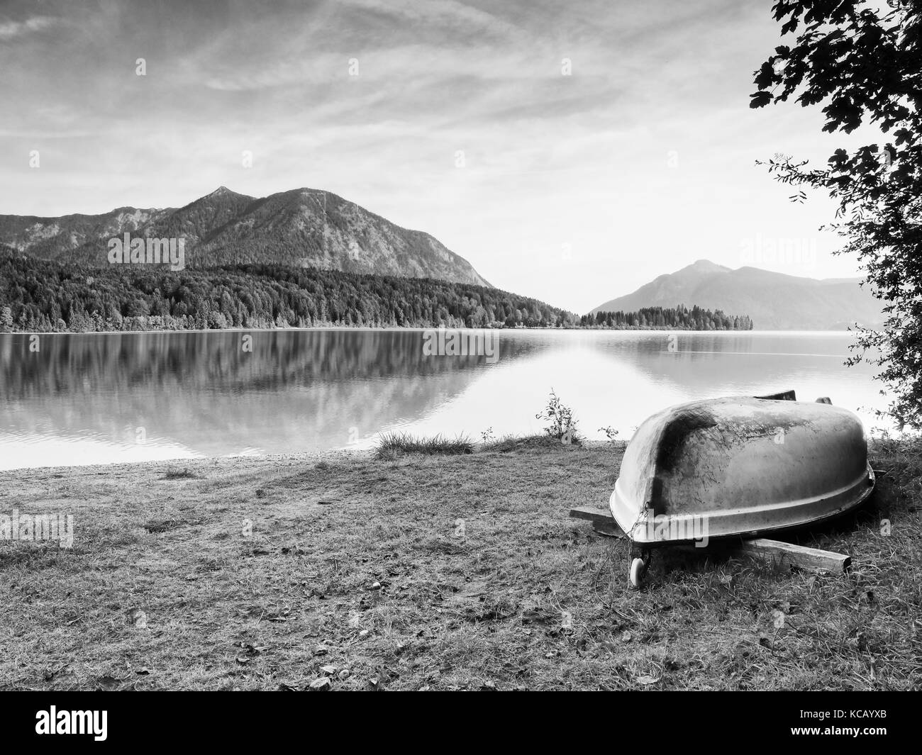 Upside down  fishing paddle boat on bank of Alps lake. Morning autumnal lake. Dramatic and picturesque scene. Mountains - Stock Image