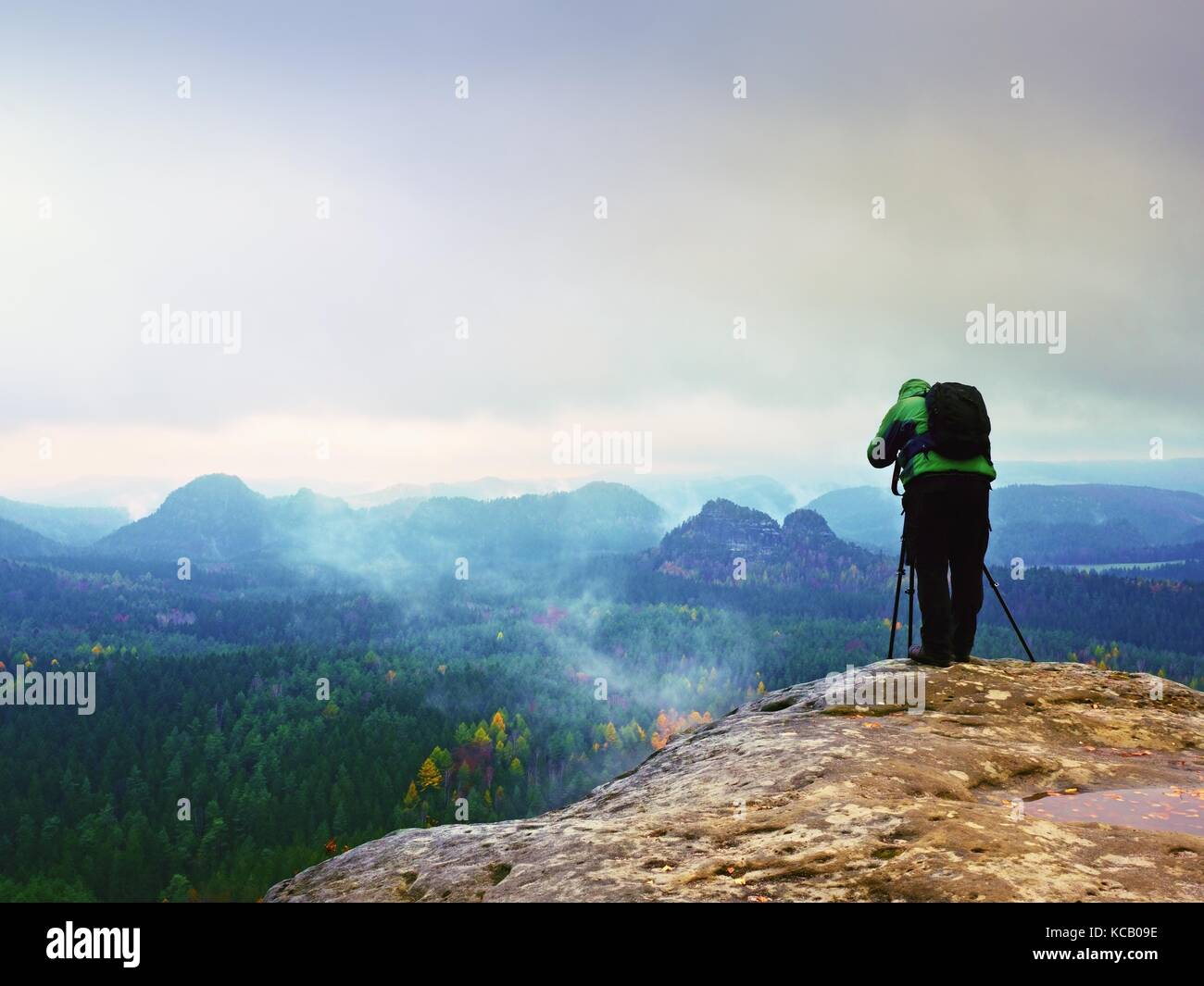 Professional photographer  in green jacket with backpack takes photos with camera on tripod on rocky peak. Dreamy - Stock Image