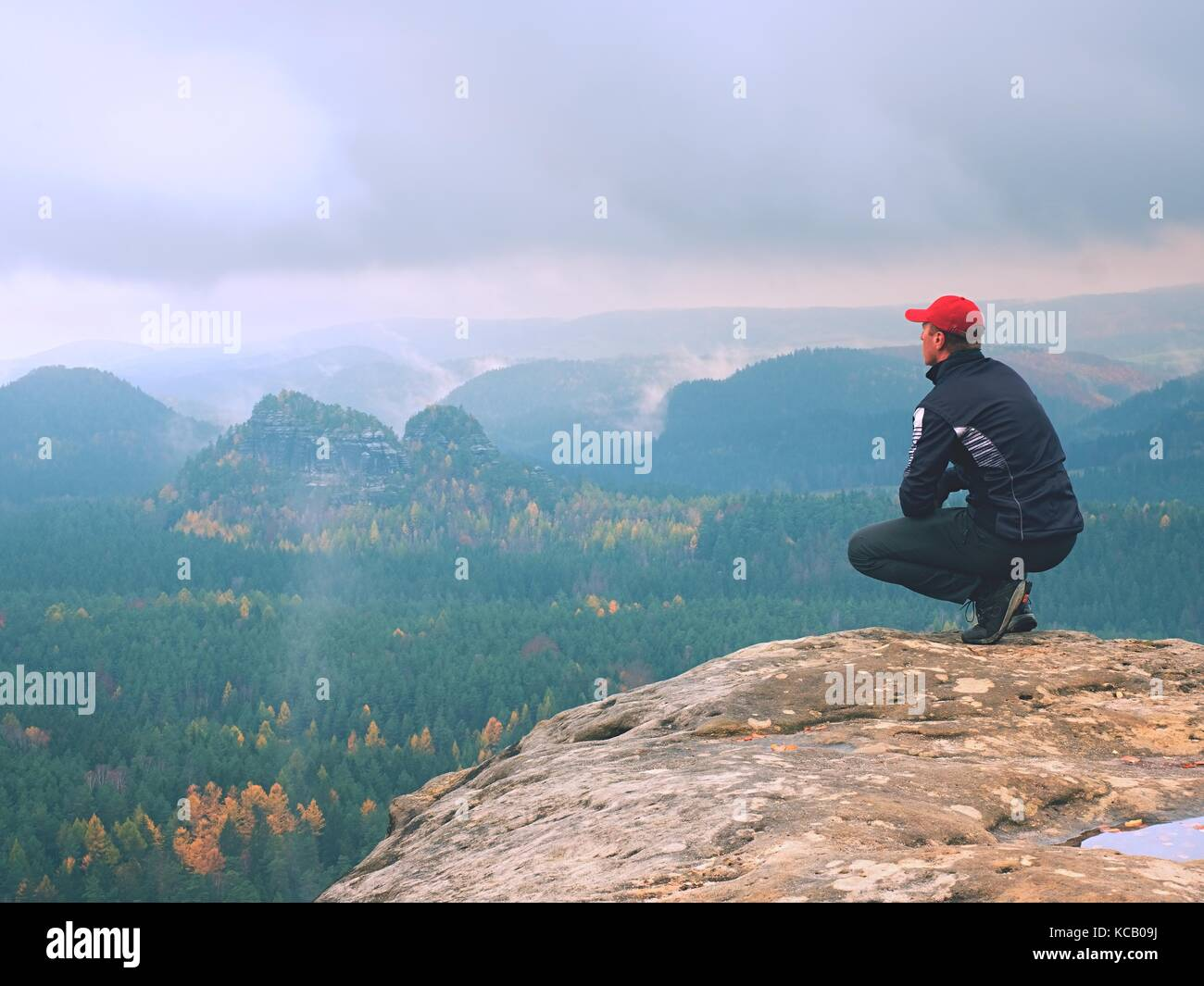 Hiker in red cap and  black sportswear in squatting position on a rock, enjoy autumn scenery. Long valley full of - Stock Image