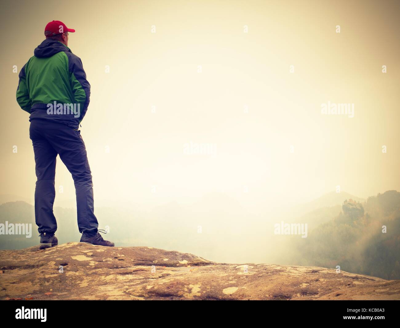 Young man in black sportswear is sitting on cliff's edge and looking to misty valley bellow. Autumn cold weather - Stock Image
