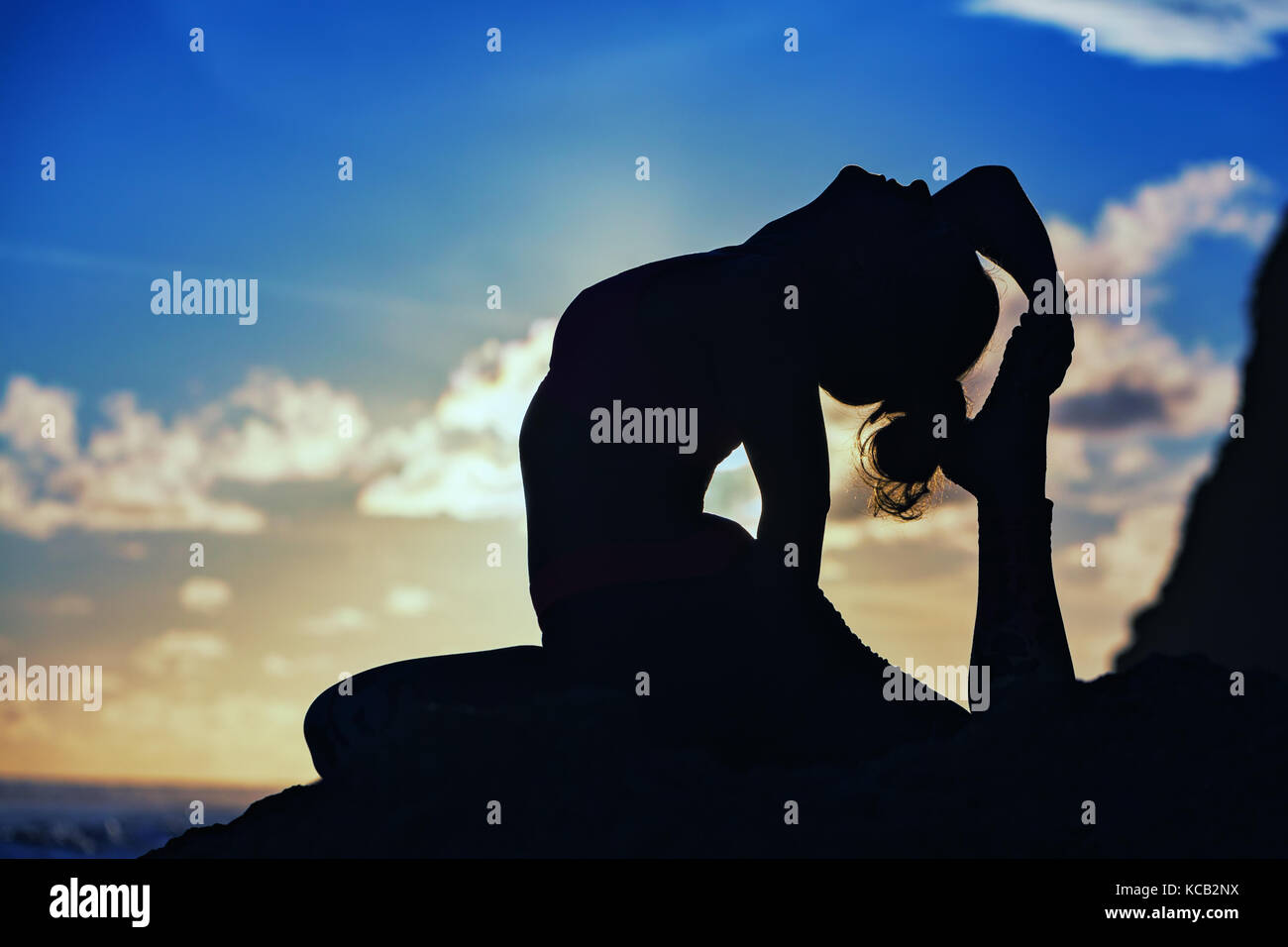 Woman black silhouette on sunset sky background. Young active girl sit in yoga pose on beach rock, stretching to - Stock Image