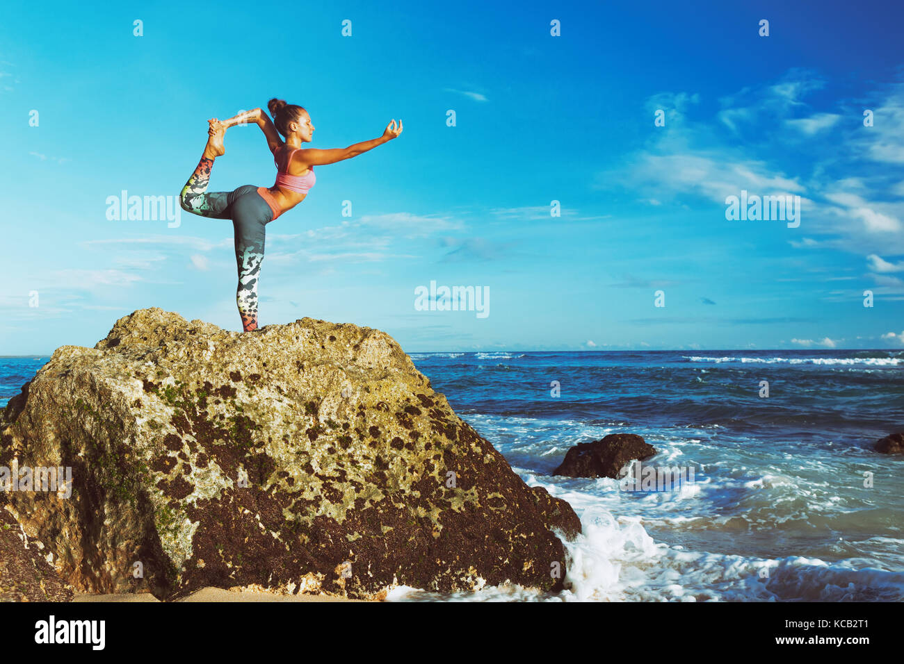 Meditation on sunset sky background. Young active woman stand in yoga pose on beach rock to keep fit and health. - Stock Image